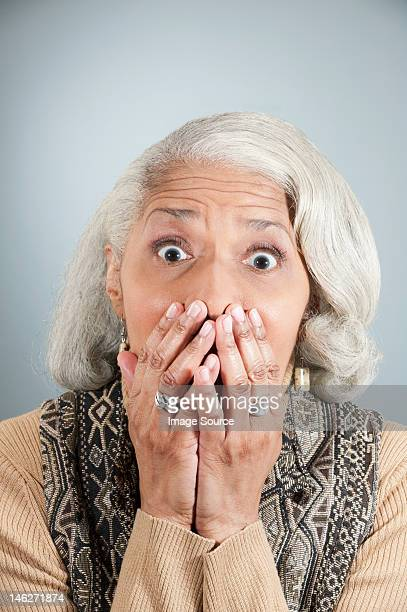portrait of senior woman covering mouth with hands in studio - hands covering mouth stock pictures, royalty-free photos & images