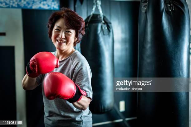 ボクサーサイズトレーニングをしている先輩女性のポートレート - 格闘技 ストックフォトと画像