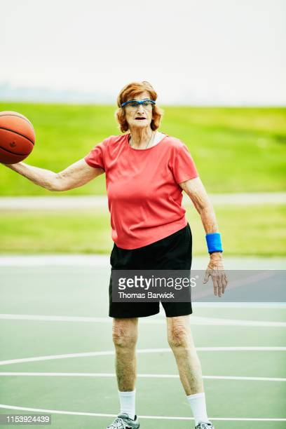 Portrait of senior woman dribbling basketball during early morning game on outdoor court