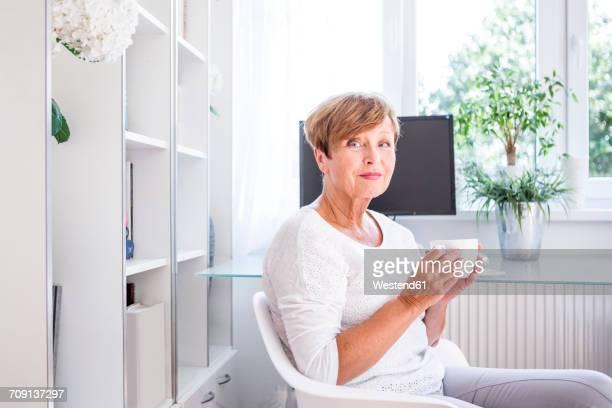 portrait of senior woman drinking cup of coffee at home - 65 69 jaar stockfoto's en -beelden