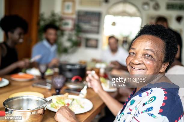 retrato da mulher sênior que come e que olha a câmera - lunch - fotografias e filmes do acervo