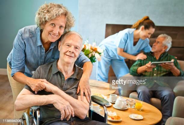 portrait of senior woman embracing disabled man - izusek imagens e fotografias de stock