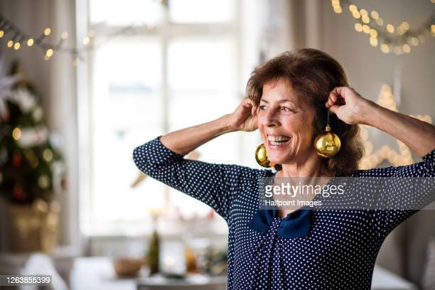 portrait of senior woman holding decorations indoors at christmas time, having fun. - earring stock pictures, royalty-free photos & images