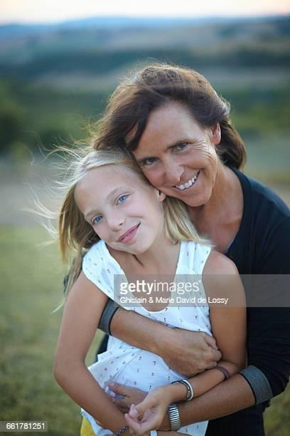 Portrait of senior woman hugging granddaughter, Buonconvento, Tuscany, Italy