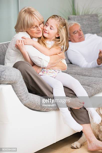 portrait of senior woman hugging granddaughter on sofa in living room - little girls in tights stock photos and pictures