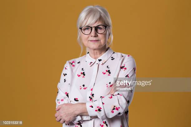 portrait of senior woman in front of coloured background - colored background stock pictures, royalty-free photos & images