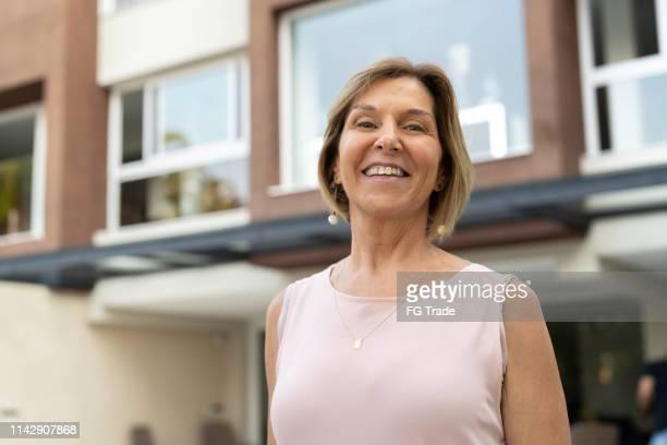 retrato da mulher sênior na frente da casa nova - foco no primeiro plano - fotografias e filmes do acervo