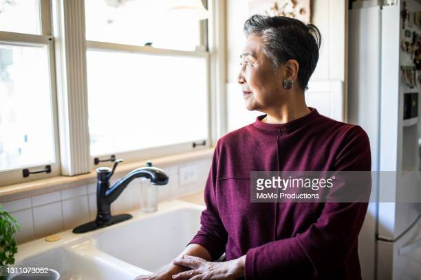 portrait of senior woman in kitchen - mortgage stock pictures, royalty-free photos & images