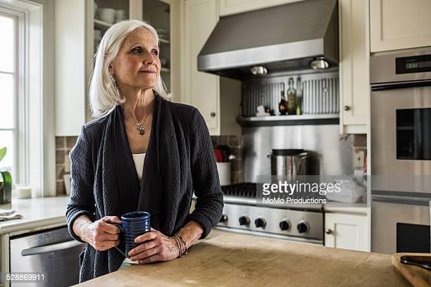 portrait of senior woman in kitchen - solo una donna anziana foto e immagini stock