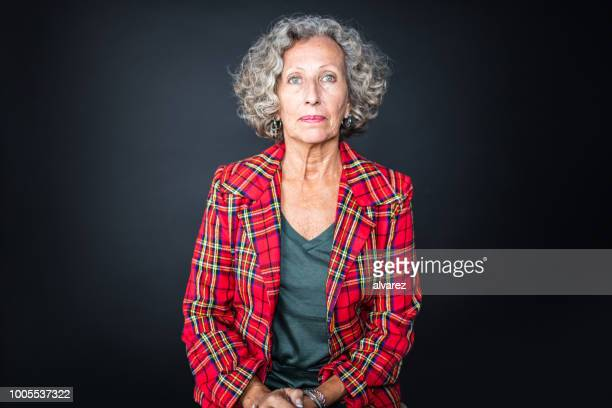 portrait of senior woman in red plaid shirt - waist up stock pictures, royalty-free photos & images