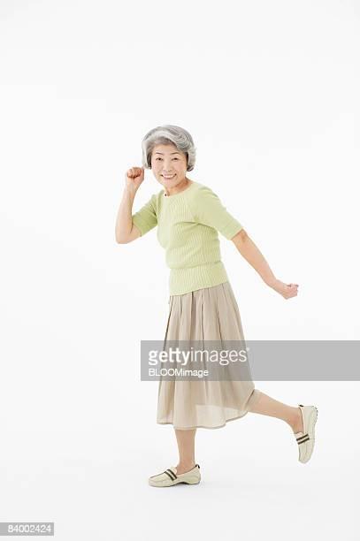 Portrait of senior woman in running pose, studio shot