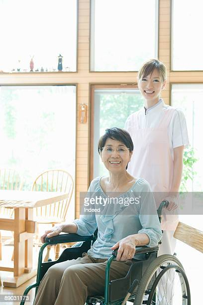 Portrait of senior woman in wheelchair and nurse