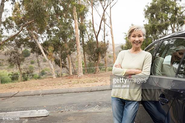 Portrait of senior woman leaning against car