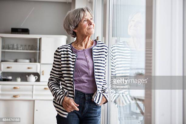 Portrait of senior woman looking through window at home