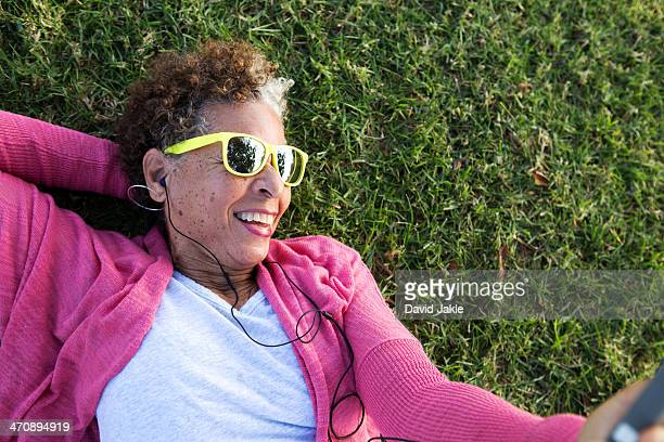 portrait of senior woman lying on grass wearing sunglasses - young at heart stock pictures, royalty-free photos & images
