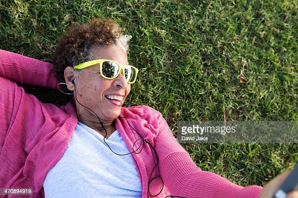 Portrait of senior woman lying on grass wearing sunglasses