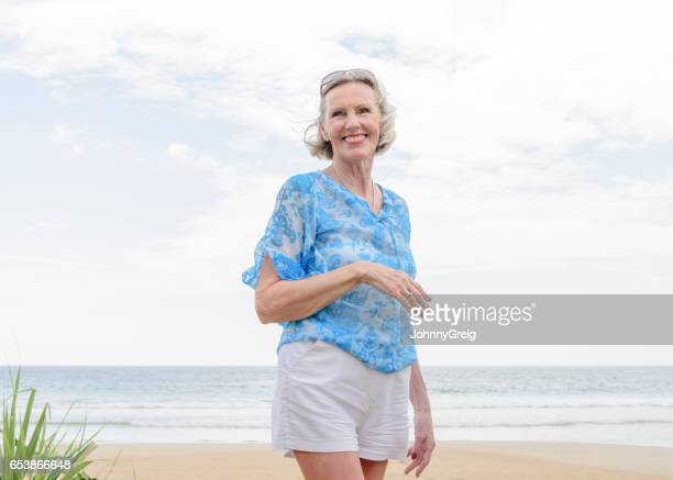 portrait of senior woman on beach smiling - blue shorts stock pictures, royalty-free photos & images