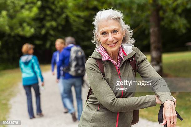 portrait of senior woman on pathway in forest - nur erwachsene stock-fotos und bilder
