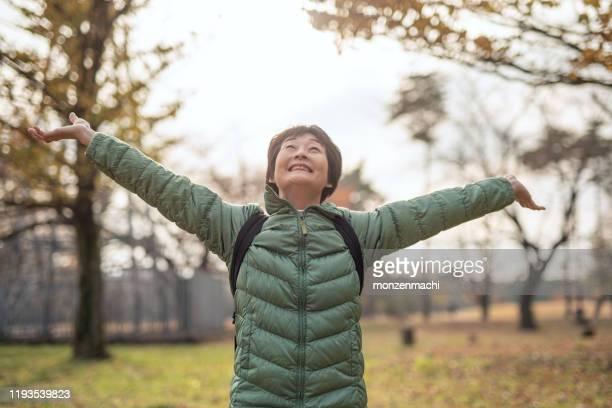 秋の公園で腕を開く先輩女性の肖像 - 息を止める ストックフォトと画像