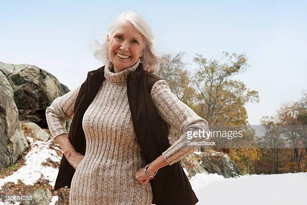 portrait de femme senior à l'extérieur, avec les mains sur les hanches - 65 69 ans photos et images de collection