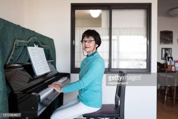 自宅でピアノを弾く先輩女性の肖像 - 趣味 ストックフォトと画像