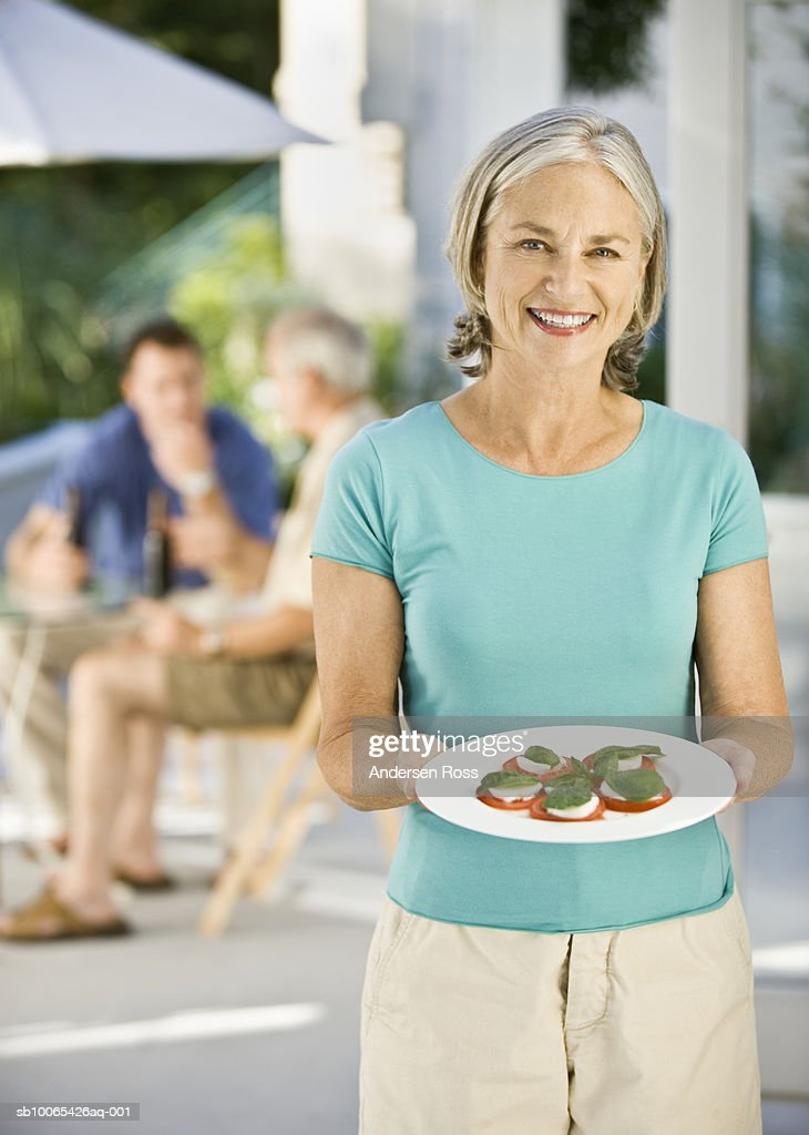 Portrait of senior woman presenting appetizers : Foto stock