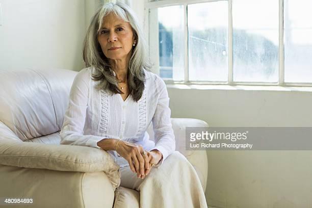Portrait of senior woman sitting in apartment