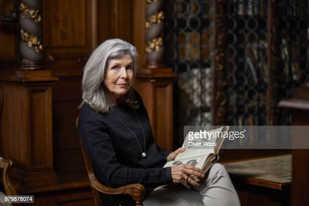portrait of senior woman sitting in chair reading book - weisheit stock-fotos und bilder
