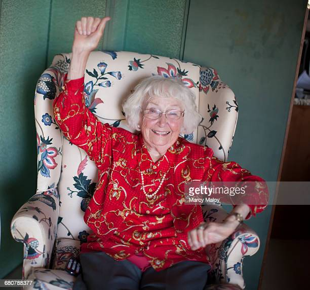 portrait of senior woman sitting in chair, smiling, arm raised - one senior woman only stock pictures, royalty-free photos & images