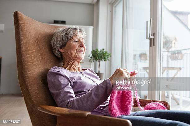 Portrait of senior woman sitting on armchair at home knitting