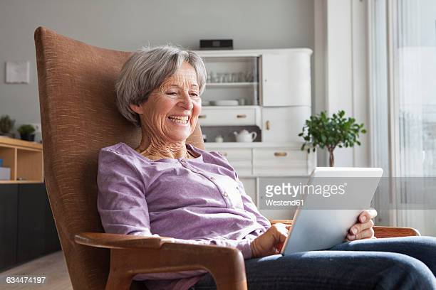 Portrait of senior woman sitting on armchair at home using digital tablet