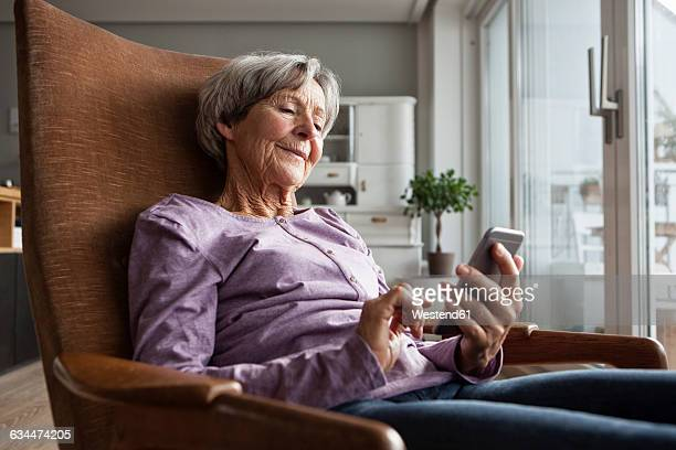 Portrait of senior woman sitting on armchair at home using smartphone