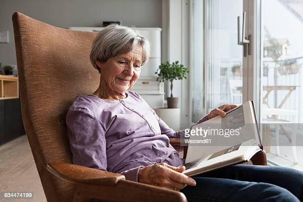 Portrait of senior woman sitting on armchair at home watching photo album