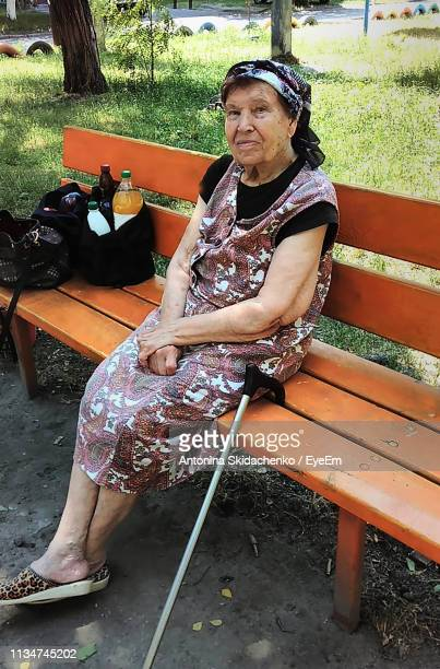 Portrait Of Senior Woman Sitting On Bench At Park