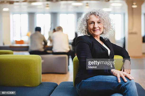 Portrait of senior woman sitting on couch at corridor