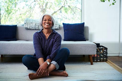 Portrait of senior woman sitting on floor at home - gettyimageskorea