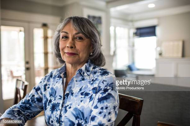 portrait of senior woman sitting on porch - latino américain photos et images de collection