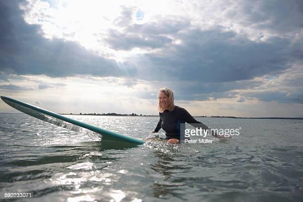 Portrait of senior woman sitting on surfboard in sea, smiling