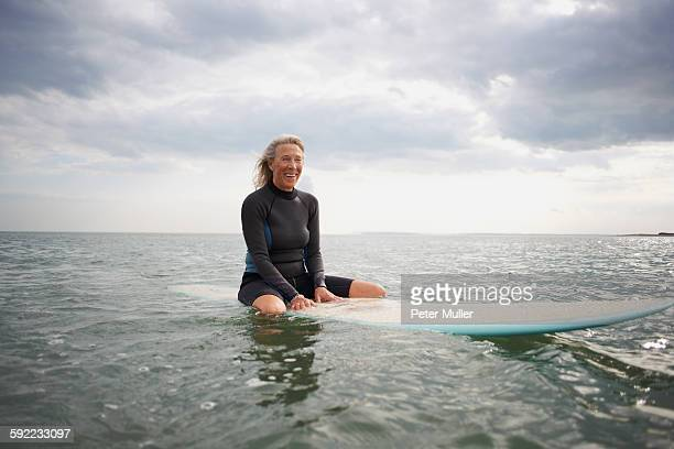 Portrait of senior woman sitting on surfboard in sea, smiling