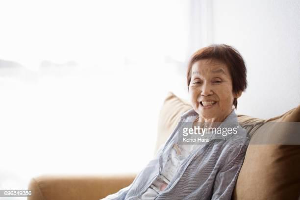 portrait of senior woman sitting on the sofa - 80代 ストックフォトと画像