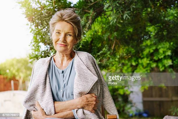 portrait of senior woman standing against tree - cardigan sweater stock pictures, royalty-free photos & images
