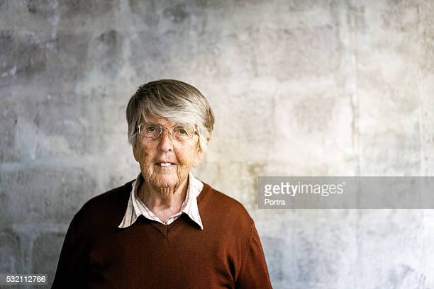 Portrait of senior woman standing against wall