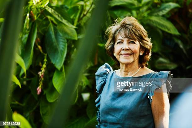 portrait of senior woman standing in backyard garden during dinner party - green dress stock pictures, royalty-free photos & images