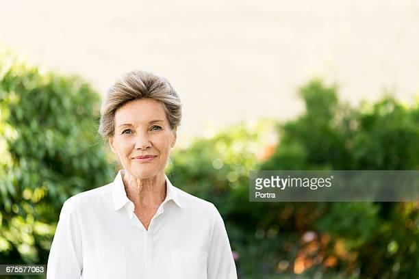 portrait of senior woman standing in yard - 65 69 anni foto e immagini stock