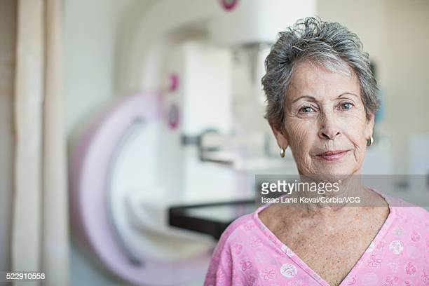 Portrait of senior woman standing near mammogram machine