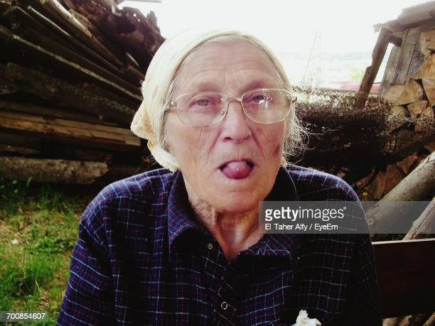 Portrait Of Senior Woman Sticking Out Tongue In Yard