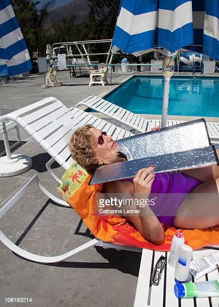 portrait of senior woman tanning her face. - bronzage humour photos et images de collection