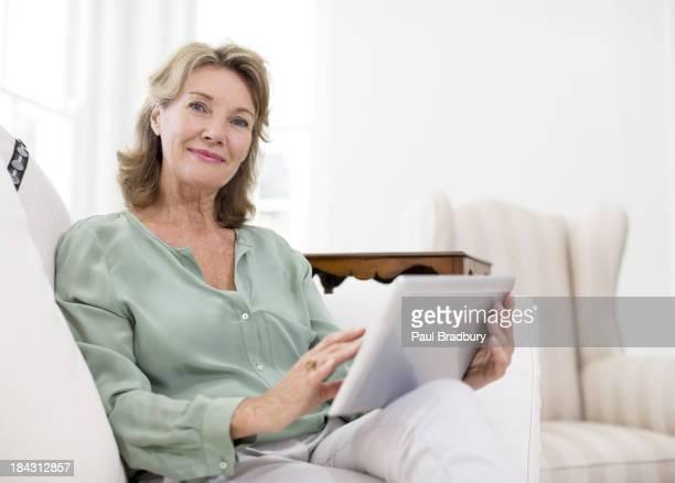 Portrait of senior woman using digital tablet on sofa