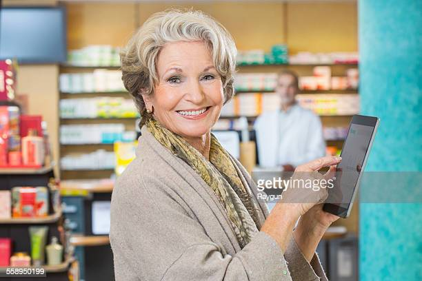 Portrait of senior woman using digital tablet to check medicine online in pharmacy