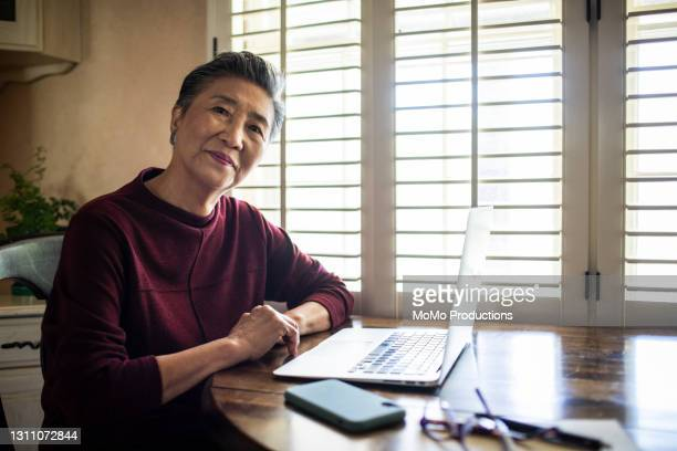 portrait of senior woman using laptop computer at home - scammer stock pictures, royalty-free photos & images
